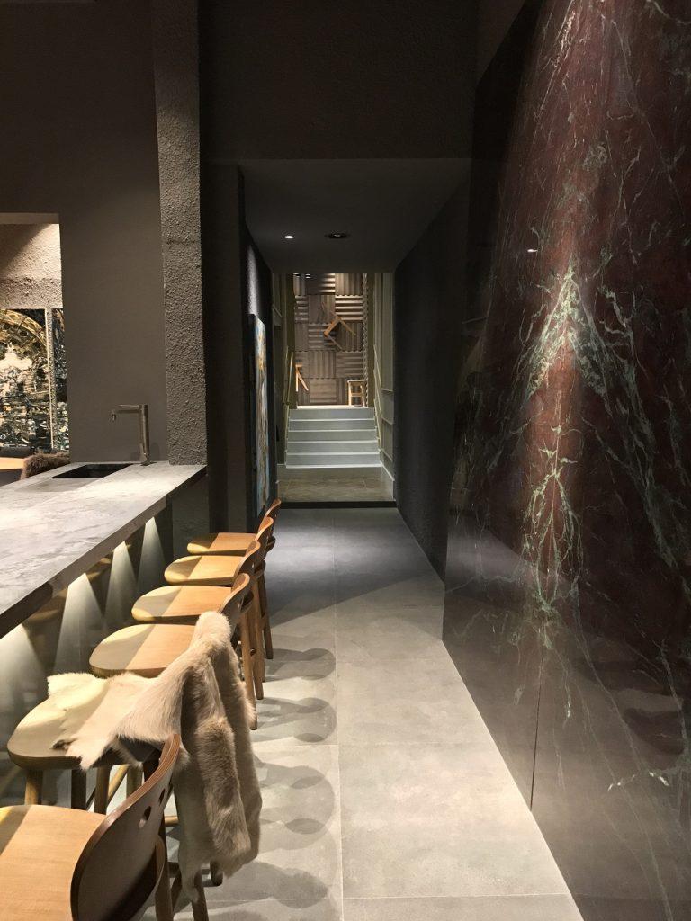 Corredor do Chef's Table, projeto do escritório DW5 Arquitetura, marcado pela parede de pedra, contracenando com peças de design e arte - eleone-prestes
