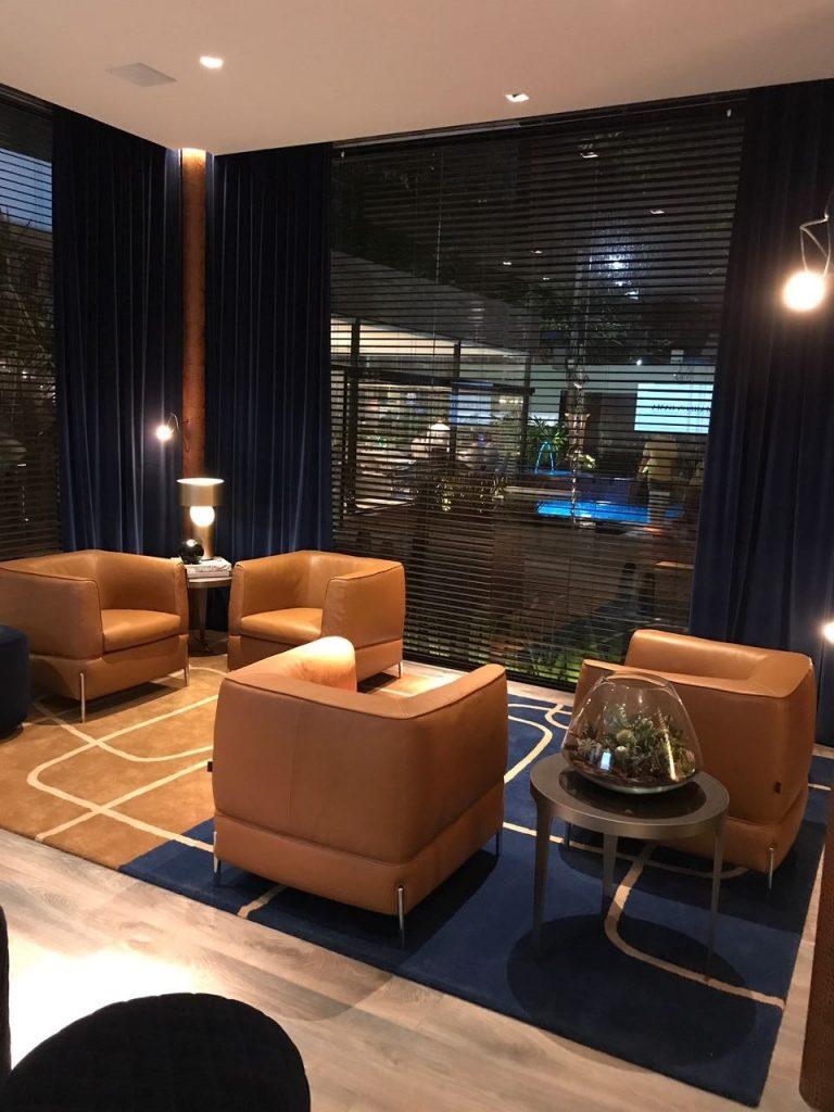 Lounge. O lounge é composto por tons caramelo e tem destaque nas almofadas do sofá e poltronas. Assim como no quarto, o tapete segue a nuance azul formando uma comunicação perfeito entre todos os ambientes. Entre os móveis que compõem os ambientes e merecem destaque, estão o sofá Herman assinado pelos arquitetos Manzoni e Tapinassi. A mesa Herman, que faz parte da coleção de mesas com acabamentos e combinações de materiais preciosos, além da poltrona Anteprima e o criado Mondrian, desenhados por Claudio Bellini.