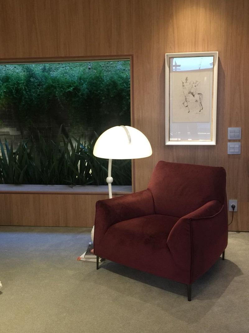 Design e arte dialogam entre a luminária, a poltrona Natuzzi e a obra na parede