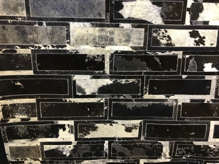 Tapetes da Raro Efeito, confeccionados de couro de vaca com pelos têm padrões inspirados em revestimentos e materiais como este, que remete a uma parede de tijolos