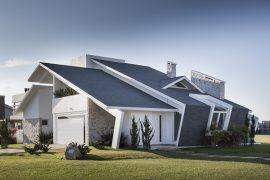 Casa com telhado inclinado que vai até o chão com telhas shingle