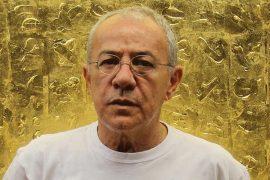 Artista Siron Franco em frente a uma obra sua