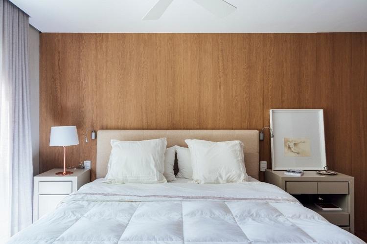 Na suíte casal, alem da integração do outro quarto para que cada um tivesse um closet, o painel que faz o fundo do closet serviu como revestimento da parede de cabeceira.