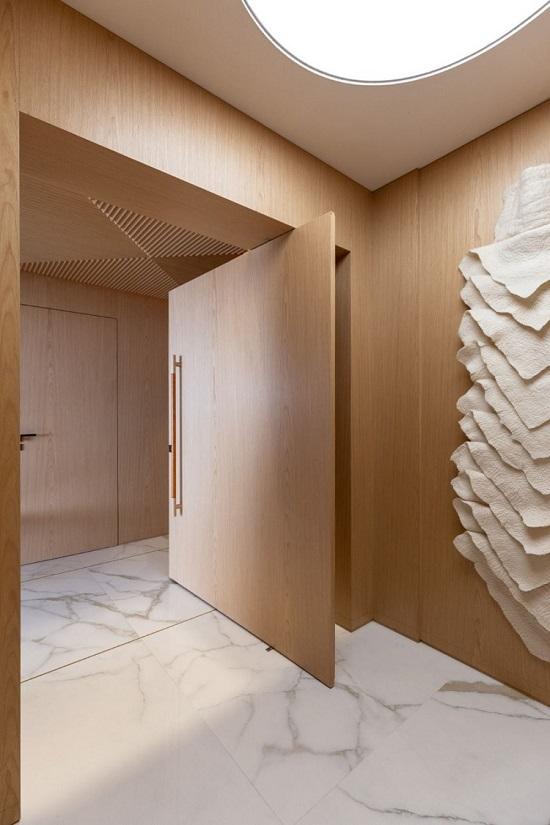 Enorme porta pivotante dá acesso ao hall social