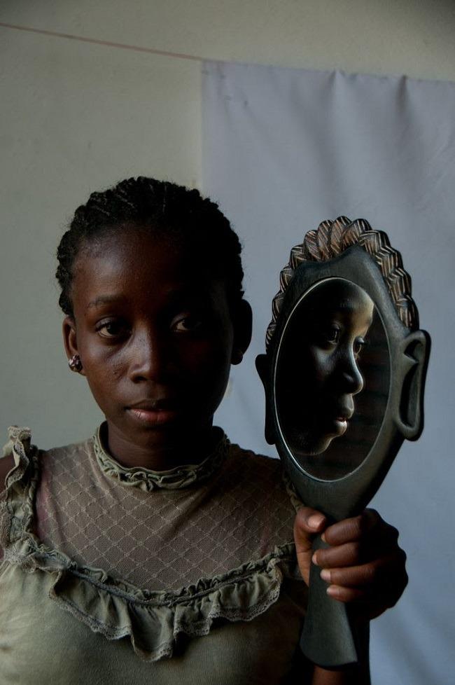 Artesã com espelho esculpido à mão em madeira, São Tomé e Príncipe