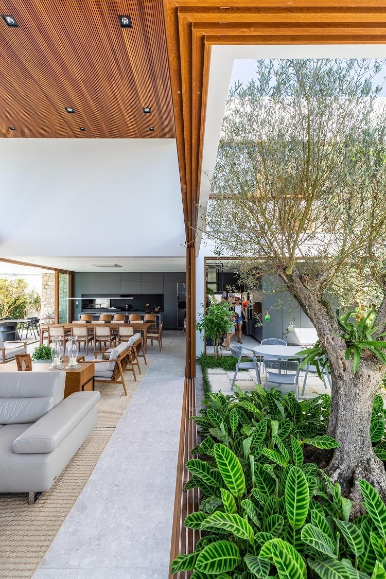 Vegetação implantada já crescida abraça até o andar superior da casa levando o frescor do verde e o visual que causa bem-estar