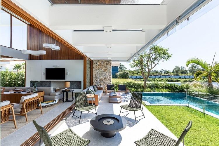 Para cada lado, uma proposta de ambiente de estar, conforme o clima e o desejo do momento na casa que oferece tanto lareira quanto piscina e ambiente externo central