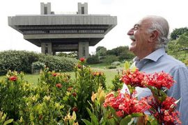 Gian Carlo Gasperini à frente de prédio que projetou, junto a um jardim florido PCV
